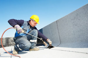 guy works on commercial TPO roofing | Robinson Roofing